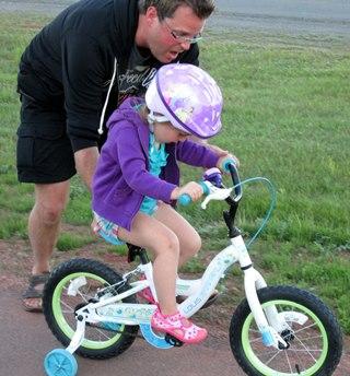 Rosalie fait l'apprentissage du vélo avec son papa Antoine.